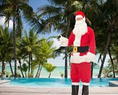 christmas, holidays, gesture, travel and people concept- man in costume of santa claus showing thumbs up over tropical beach and swimming pool background