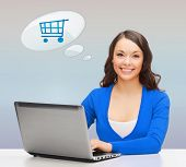 online shopping, people and technology concept - smiling young woman with laptop computer over gray background and trolley