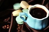 Gentle colorful macaroons and black coffee in mug on color fabric background