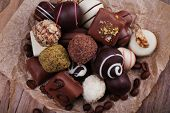 Chocolates assorted on crumble paper with coffee beans on wooden rustic background