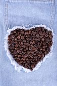 Heart from a handful of coffee beans on the jeans background