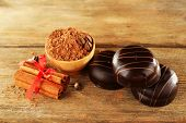 Chocolate cookies with bowl of cocoa and cinnamon on rustic background