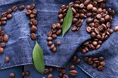 Green petal with coffee beans on blue wooden background with jeans material