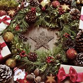 a rustic wooden table full of gifts, and christmas ornaments, such as a natural wreath with branches, berries and pine cones, or christmas balls and stars , with a retro effect