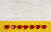Old wooden white background with seven red hearts on the yellow frame with white dots.