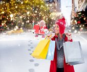 Blonde in winter clothes holding shopping bags against santa delivering gifts in city