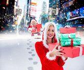 Festive blonde holding pile of gifts against santa delivering gifts in city