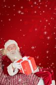 Father christmas offering a red gift against red background