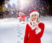Festive blonde holding a mug against santa delivering gifts in city