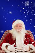 Santa holding his belly on the armchair against red background