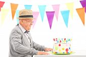 Happy senior sitting at a table with birthday cake isolated on white background