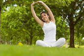Healthy and beautiful young woman stretching hands in park