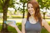 Pretty redhead holding a bottle of water in park