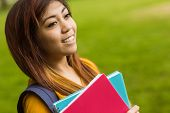 Close up of smiling female college student with books in the park