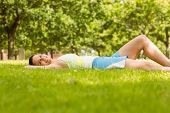 Happy fit brunette lying and relaxing on the grass in the park