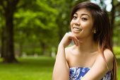 Portrait of beautiful young woman with hand on chin in park