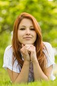 Pretty redhead thoughtful and lying on grass in park