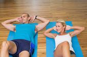 High angle view of a sporty young couple doing abdominal crunches at fitness studio