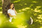 Pretty redhead on the phone holding her laptop in park on a sunny day
