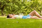 Cheerful fit brunette lying and relaxing on the grass in the park