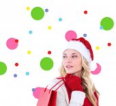 Happy festive blonde with shopping bag against dot pattern