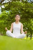 Full length of healthy and beautiful young woman sitting in lotus pose at park