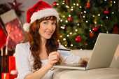 Smiling redhead shopping online with laptop at home in the living room