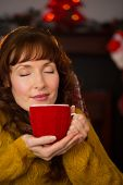 Pretty redhead enjoying hot drink at christmas at home in the living room