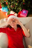 Smiling redhead making heart with her hands at home in the living room