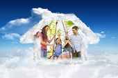 Happy couple pushing kids on swing against bright blue sky with clouds