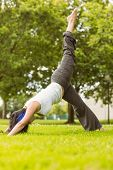 Peaceful brown hair doing yoga on grass in the park