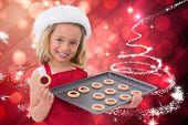 Festive little girl holding fresh cookies against glittering christmas tree design