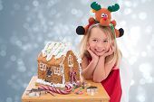Festive little girl making gingerbread house against light design shimmering on silver