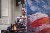 NEW YORK - NOV 11, 2014: American artist Scott LoBaido paints an American Flag on a large canvas in real time during the 2014 America's Parade on Veterans Day in New York City on November 11, 2014.