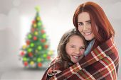 Mother and daughter under blanket against blurry christmas tree in room
