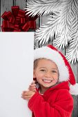 Festive little girl showing poster against wood with festive bow