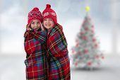 Cute girls under blanket against blurry christmas tree in room