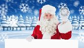 Santa claus holding alarm clock and sign against snowy landscape with fir trees