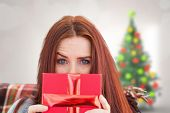 Woman holding gift against blurry christmas tree in room