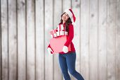 Happy brunette holding many gifts against blurred wooden planks