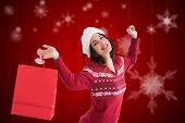 Content brunette holding shopping bag against blurred snowflakes