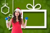 Festive fit brunette holding dumbbells against blurred christmas background