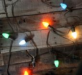 Genuine Vintage 1950s era colored Christmas Lights against Vintage de-nailed rustic and weather beaten old wooden planks for an authentic Vintage Christmas look and feel. Perfect for all your needs
