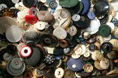 Piles and Piles of beautiful and colorful used buttons of various articles of clothing and save in a box for future sewing or art projects. Buttons are an important part of the sewing process