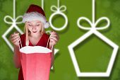 Festive blonde opening a gift bag against blurred christmas background