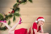 Festive blonde smiling at camera against blurred holly on wood