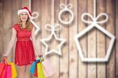 Pretty woman in santa hat standing with shopping bags against blurred christmas decorations on wood