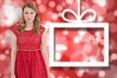 Beautiful woman wearing red dress smiling at camera against blurred christmas background
