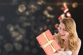 Cute blonde holding a gift against shimmering christmas tree of lights