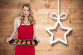 Pretty blonde showing hot cookies against blurred christmas decorations on wood